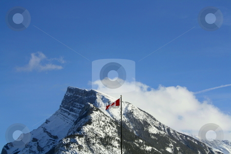 Canadian Flag Flying Over The Rocky Mountains stock photo, Canadian Flag flying over the snowy Rocky Mountains with sky and clouds by CHERYL LAFOND