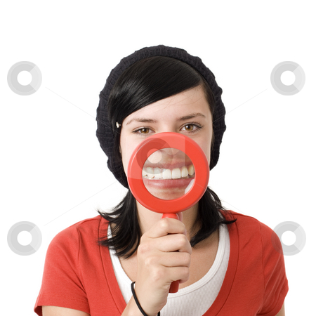 Magnified teeth teenager stock photo, Girl shows teeth with magnifying glass by Rick Becker-Leckrone