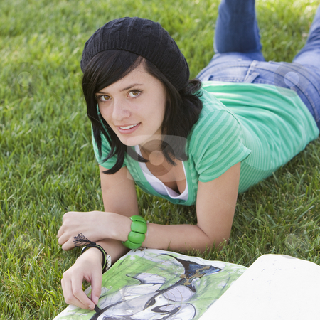Teen sketches in grass stock photo, Teen draws in a sketch book while lying in grass by Rick Becker-Leckrone
