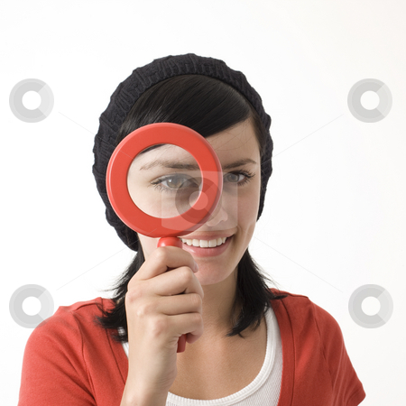 Girl with magnifying glass stock photo, A girl holds up a magnifying glass to her eye by Rick Becker-Leckrone
