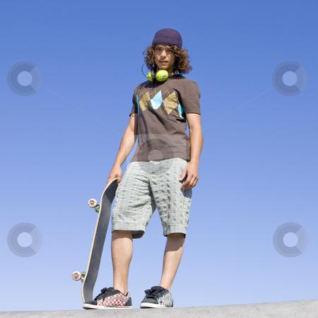 Teen skater atop ramp stock photo, Teen skater stands atop ramp by Rick Becker-Leckrone