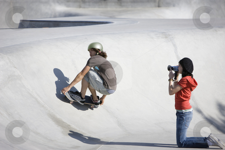 Videotaping skateboard action stock photo, Boy dies tricks at the skateboard park as girl videotapes by Rick Becker-Leckrone