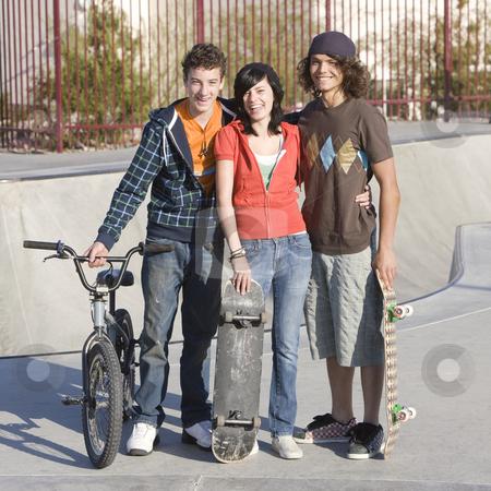 Three teens at skatepark stock photo, Three kids hang out at the skatepark by Rick Becker-Leckrone