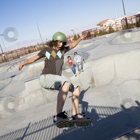 Tricks at the skatepark stock photo, Teen skater does tricks at the skate park with his friends by Rick Becker-Leckrone