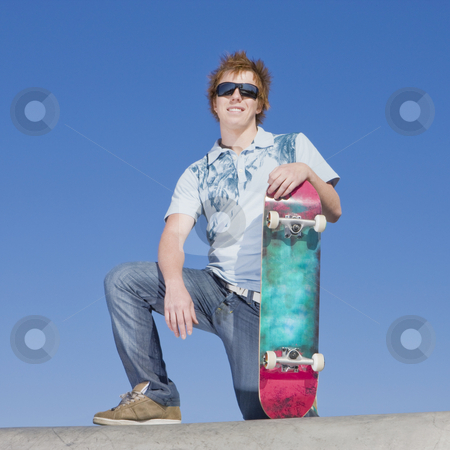 Teen skater atop ramp stock photo, Teen skater kneels atop ramp by Rick Becker-Leckrone