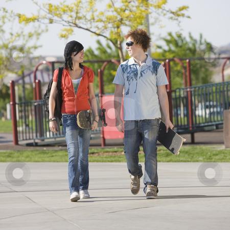 Teens couple walks stock photo, Two kids walk home through a park by Rick Becker-Leckrone