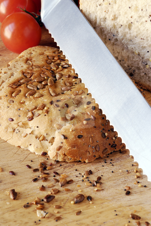 Seeded bread on wooden board stock photo, Sliced seeded bread with close up of serrated bread knife by Paul Turner