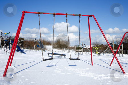 Child's swings in an empty park playground covered in snow. stock photo, Child's swings in an empty park playground covered in snow. by Stephen Rees
