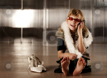 Cute young girl in red glasses talking on cell phone stock photo, Cute young girl in dress-up clothes and red sunglasses talking on cell phone by Scott Griessel