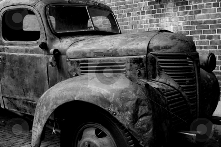 Battered Truck stock photo, Black and white photograph of a battered truck with a brick wall background. by Wes Shepherd