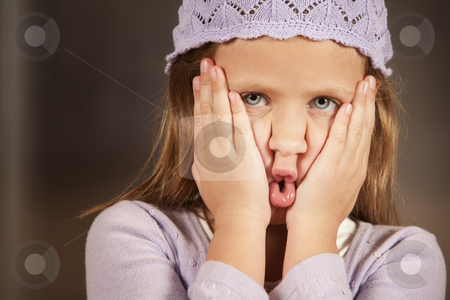 Young girl making a funny face stock photo, Cute young girl in a knit cap making funny face by Scott Griessel
