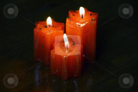 Burning candles stock photo, Three orange burning star shape candles on dark wooden background by Julija Sapic