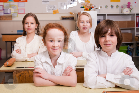 Sitting in the classroom stock photo, Group of little students with different ages in a classroom by Frenk and Danielle Kaufmann