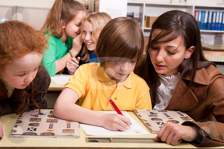 The teacher helps stock photo, Group of little students with different ages in a classroom by Frenk and Danielle Kaufmann