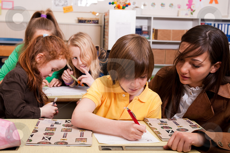 The helping teacher stock photo, Group of little students with different ages in a classroom by Frenk and Danielle Kaufmann