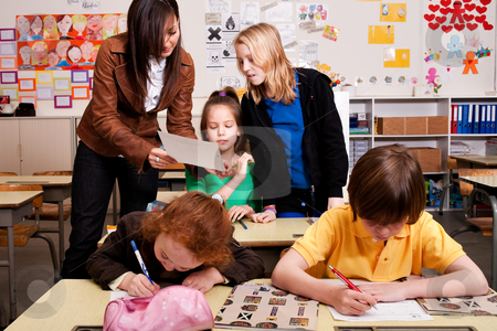 Teacher is correcting the piece of paper stock photo, Group of little students with different ages in a classroom by Frenk and Danielle Kaufmann
