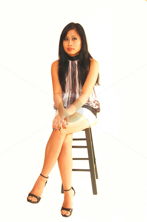 Young Asian girl sitting. stock photo, An young Asian girl in a nice top and white short skirt, long black hair  sitting on a bar chair in an studio for white background. by Horst Petzold