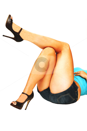 Nice legs laying on the floor. stock photo, An young woman in short jeans shorts is laying on the floor in high heel and showing her beautiful legs. by Horst Petzold