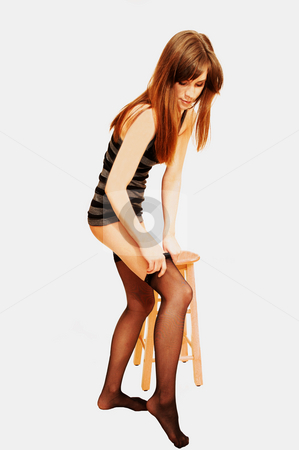 Young lady in underwear. stock photo, A young pretty lady standing on an bar chair in stockings bra and panties on light blue background. by Horst Petzold