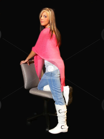 Young lady in jeans. stock photo, An young lady in jeans and a pink top standing for black background on an office chair. by Horst Petzold