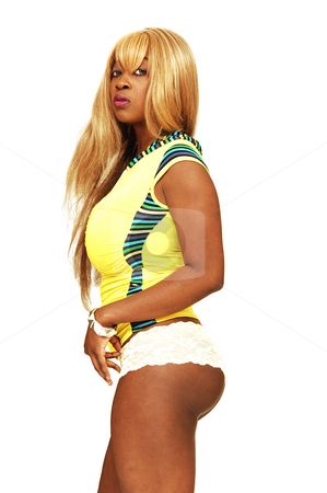 Young Jamaican girl. stock photo, An busty young Jamaican girl in a yellow top, long blond hair and in panties standing in an studio for a nice portrait. by Horst Petzold