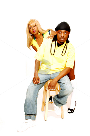 Young black couple. stock photo, A young African American couple, he is sitting on a bar chair and she  standing behind him in the studio for white background. by Horst Petzold