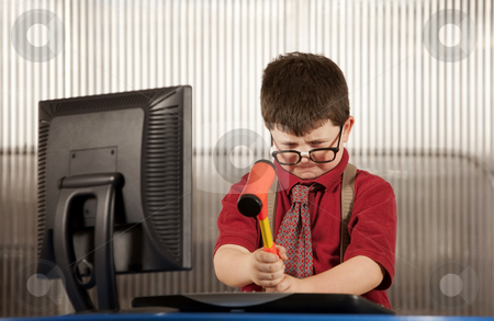 Nerdy boy smashing his computer stock photo, Nerdy young boy smashing his computer with a hammer by Scott Griessel