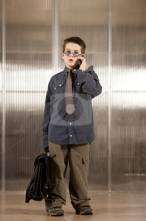 Little boy in adult clothes on cell phone stock photo, Handsome young boy in adult business clothes on phone by Scott Griessel