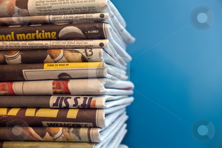 Newspapers stock photo, A stack of newspapers with a blue background by Norma Cornes