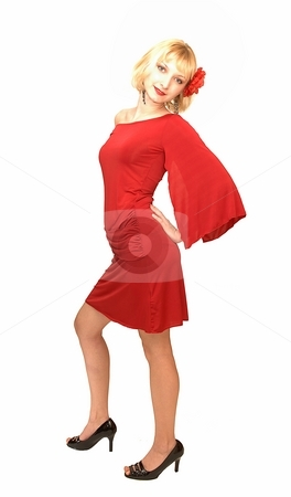 Standing blond woman in red dress. stock photo, An friendly blond girl in an short red dress standing in an studio  for white background with a red flower in her hair.. by Horst Petzold