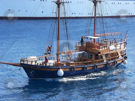Old wooden sailboat. stock photo, An sailboat made from wood in the front of an big cruise ship the  Mediterranean sea. by Horst Petzold