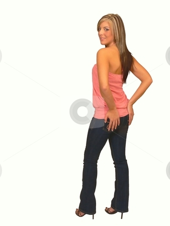 Young lady in jeans. stock photo, An young lady in jeans and a pink top standing for black background and holding her bottom. by Horst Petzold