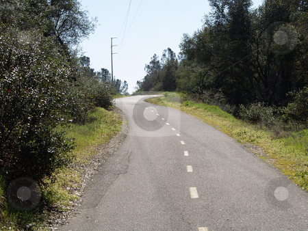 Paved bike path up hill with trees and power lines stock photo, Empty bike path lined by trees and bushes goin up hill by Jeff Cleveland