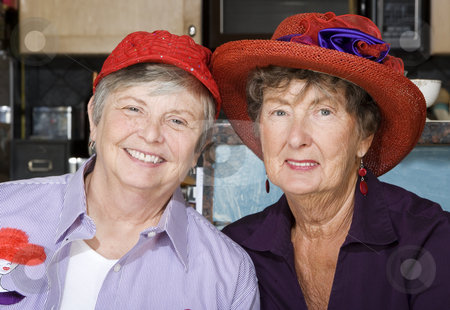 Two Senior Women Wearing Red Hats stock photo, Two friendly senior women wearing red hats by Scott Griessel