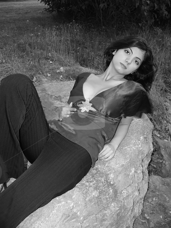 Young girl laying on the rock   stock photo, A lovely girl in blouse and pants is laying on the rock in black by Horst Petzold