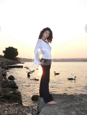 Lady on the lake in sunset   stock photo, An lovely young lady standing  on a big rock on the lake relaxing by sunset. by Horst Petzold
