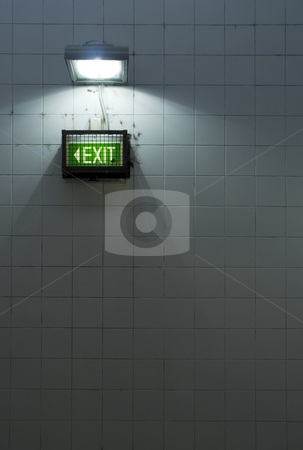The Exit stock photo, A grungy subway exit sign on a tiled wall by Stephen Gibson
