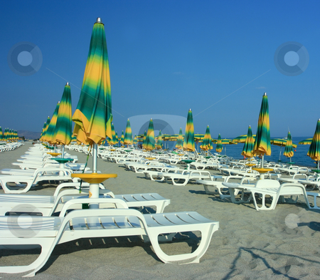 Beach with folded umbrellas stock photo, Beach with colorful folded umbrellas before sunset by Natalia Macheda