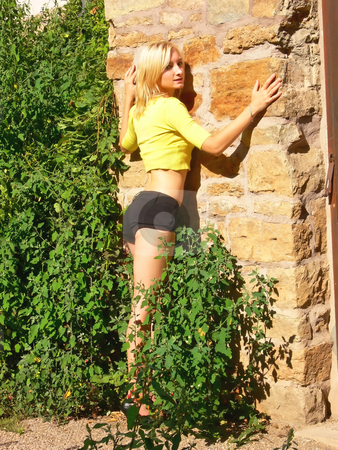 Blond lady on an stone wall. stock photo, An beautiful blond young lady in short black pants and an yellow top standing on the stone wall of an very old building. by Horst Petzold