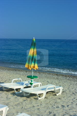 Folded umbrella on a beach stock photo, One folded umbrella and two chaise-longue by Natalia Macheda