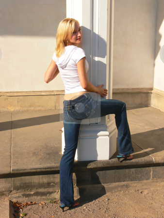 Blond lady on white column. stock photo, An pretty young blond lady in jeans and an white top standing on an white column on an old mansion. by Horst Petzold