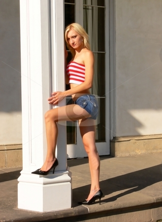 Lady standing on an pillar. stock photo, An young beautiful lady is sitting on the steps of an old mansion wearing an red and white striped top and short jeans shorts. by Horst Petzold