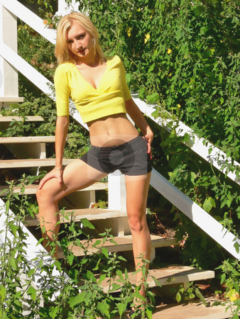 Lady standing on white wooden steps. stock photo, An young beautiful lady is standing on white steps with an yellow top and and black short shorts. by Horst Petzold