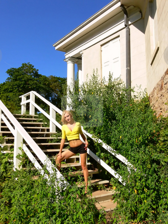 Lady standing on white wooden steps. stock photo, An young beautiful lady is standing on the steps of an old mansion wearing an yellow top and black short shorts. by Horst Petzold