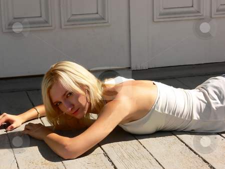 Young girl in white blouse. stock photo, An young lady in short jeans and a white blouse lying on the floor  in front of the entrance of an mansion. by Horst Petzold
