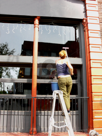 Window cleaner. stock photo, An girl is standing on a ladder and cleaning the outside windows of an restaurant in bright sunshine. by Horst Petzold