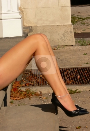 Long beautiful legs. stock photo, The long beautiful legs with black high heels sitting on the steps of an big house. by Horst Petzold