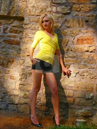 Lady on the wall. stock photo, An young lady standing on an old stone wall in short black shorts and yellow sweater. by Horst Petzold