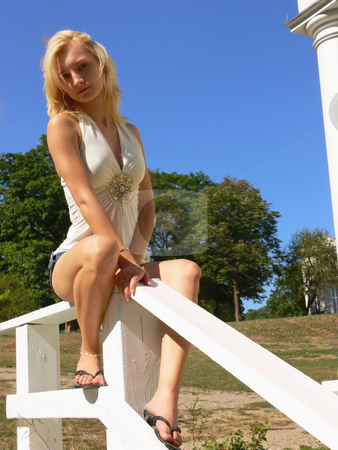 Sitting on the handrail. stock photo, An pretty blond young lady sitting on the hand rail with blue sky in the background. by Horst Petzold