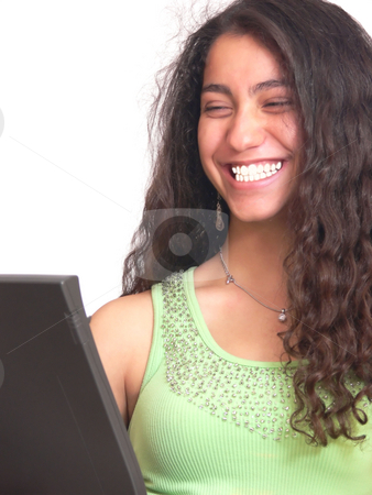 Busy young girl   stock photo, A young girl laying on the floor with her nice long curly dark hair working on the laptop and looks up to the camera. On white background. by Horst Petzold